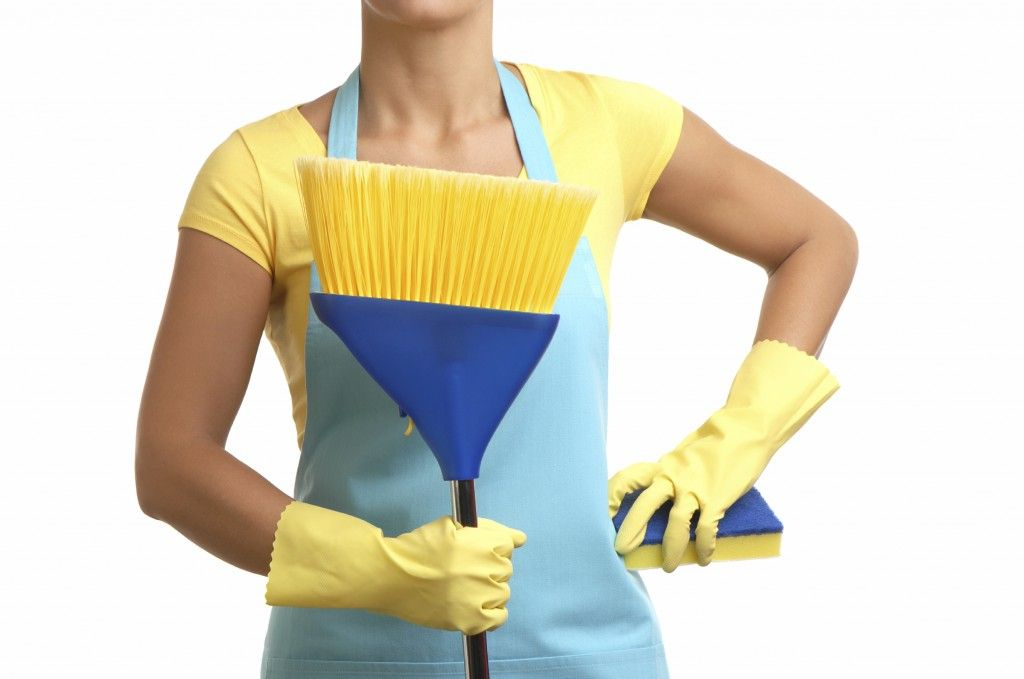 Maid in blue holding a broom and a sponge