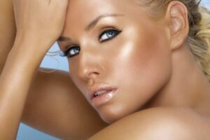 Young tanned woman with blond hair.