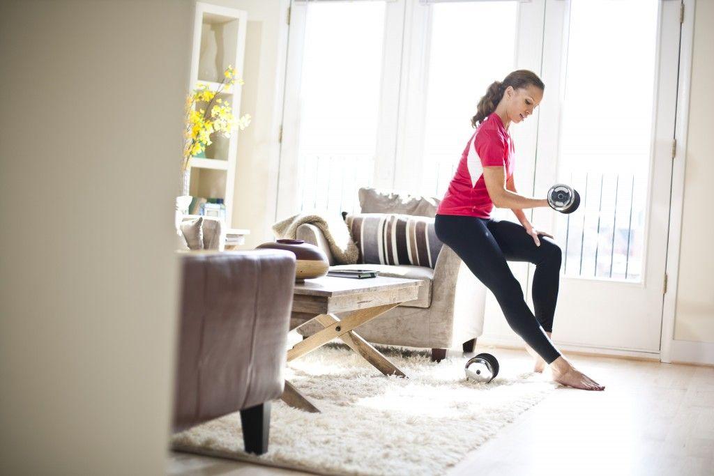Woman exercising in living room --- Image by © Artiga Photo/Corbis