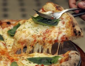 A slice of Margherita pizza is served at Braz pizzeria in Sao Paulo, September 28, 2007. Sao Paulo is home to more than 6,000 pizza parlors that, in all, churn out close to a million pies a day, according to the local association of pizzerias. By some estimates, only New Yorkers devour more pizzas annually than Paulistanos. Picture taken September 28, 2007.    REUTERS/Paulo Whitaker (BRAZIL)